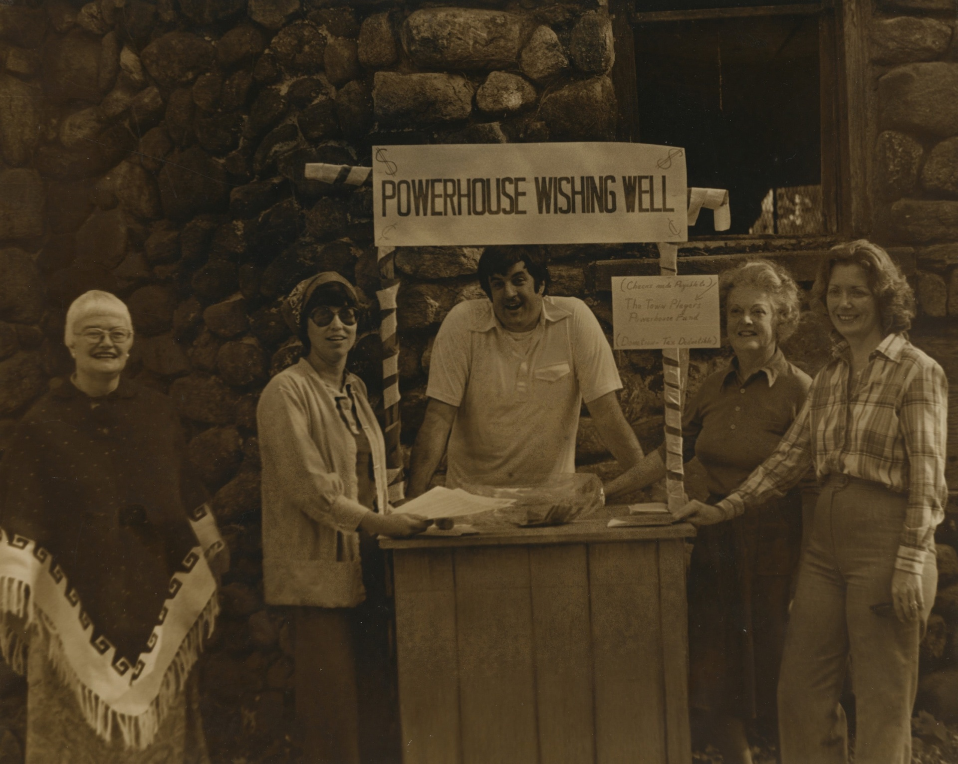 """Sepia-toned picture of five volunteers around a stand reading """"Powerhouse Wishing Well"""""""